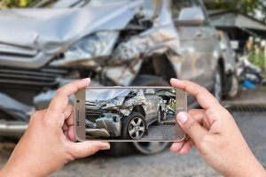 Person taking a picture of a damaged car after accident with phone