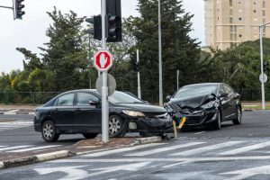 two black cars that hit each other are in the middle of a street